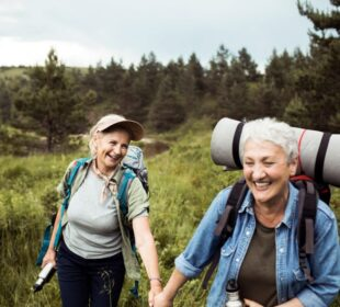 A lesbian couple hike together. This photo is meant to represent taking social security out based on your spouse.